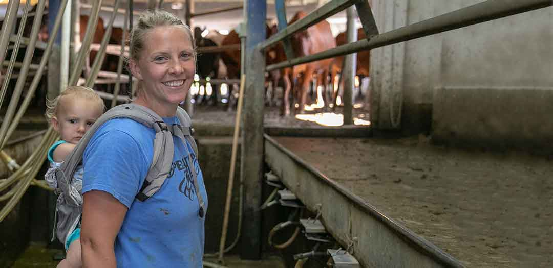 A woman with a baby on her back in a dairy farm milking barn. Photo credit Finn Ryan
