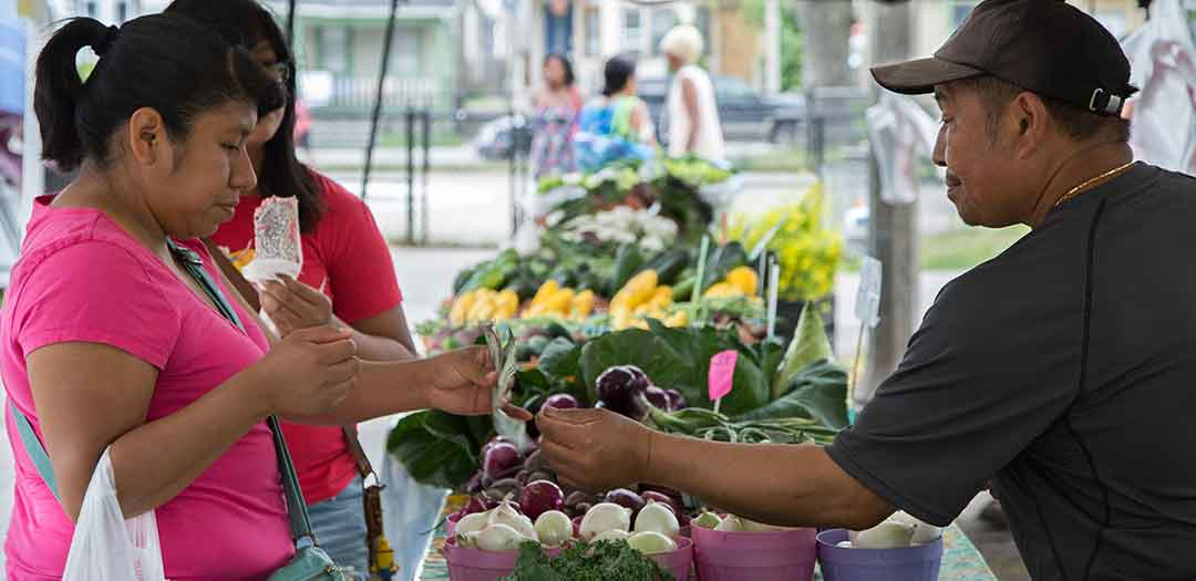 A woman buying vegetables at a farmers market. Photo credit UW Madison Division of Extension