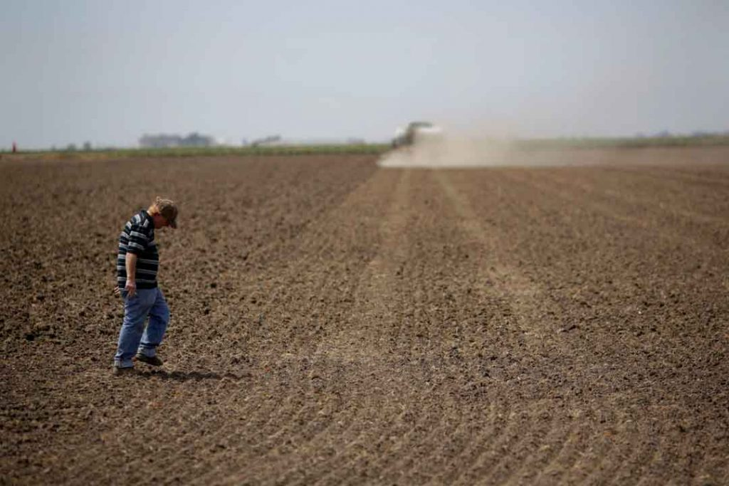 A man walking across a plowed dirt field with a plow in the background